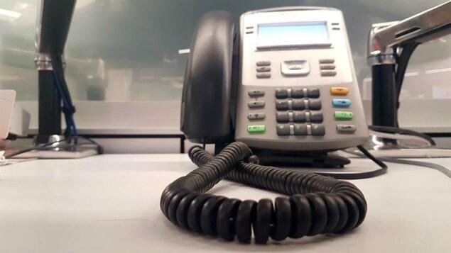 Un téléphone filaire devant un paravent.