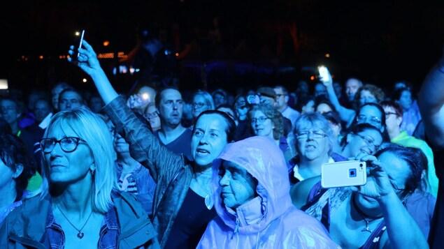 Gens avec leurs téléphones cellulaires durant le spectacle de Michel Fugain.
