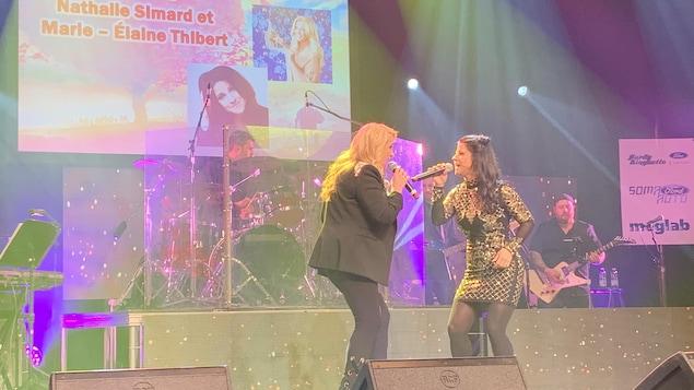 Deux femmes chantent sur une scène. Des musiciens jouent derrière elles.