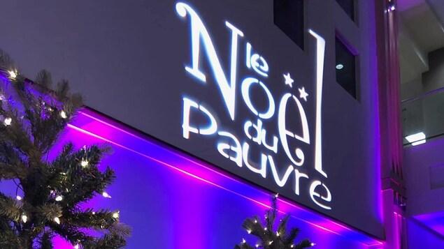 Le logo du Noël du Pauvre et des arbres illuminés.