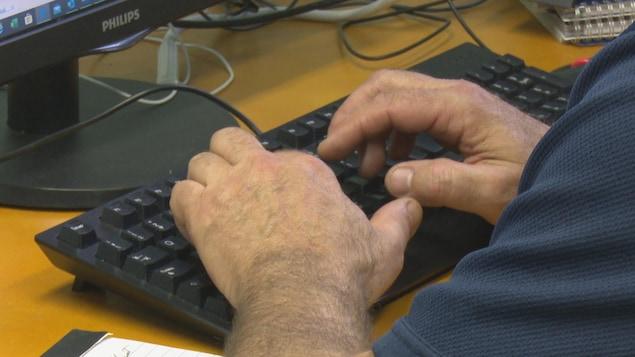 Un homme travaille avec un ordinateur.