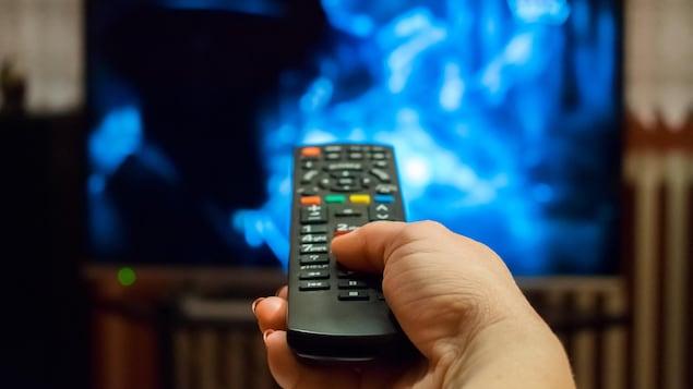 Une main tient une télécommande devant un écran de télévision.