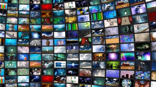 Des écrans de télévision tapissent un mur.