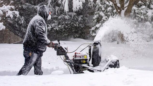 Un homme passe la souffleuse après une tempête de neige en périphérie de Boston le 17 décembre 2020.