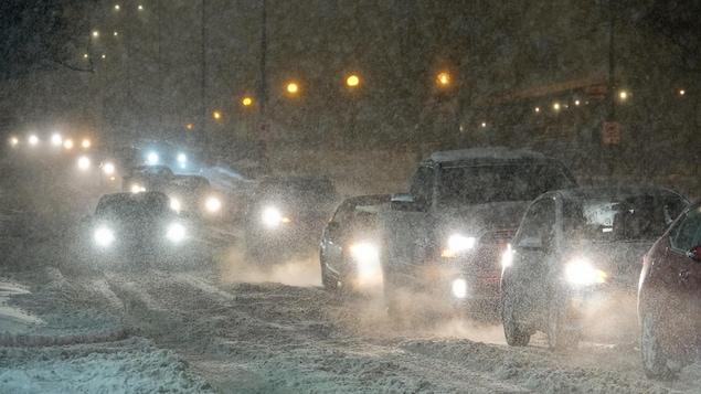 Des voitures à la queue leu-leu sous la neige.