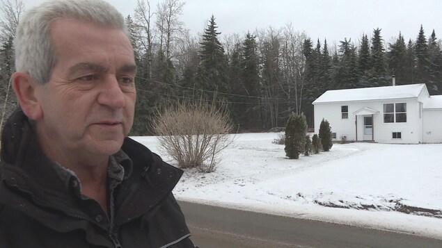 L'homme en entrevue devant sa maison inondée.
