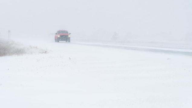 Un camion roule sur une route enneigée