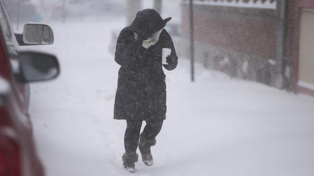 Une femme marche tête baissée dans le vent et la neige en tenant un gobelet de café.