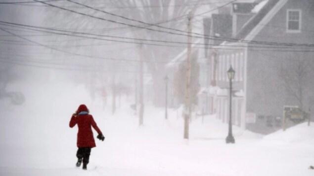 Une femme vue de dos qui marche dans la tempête.