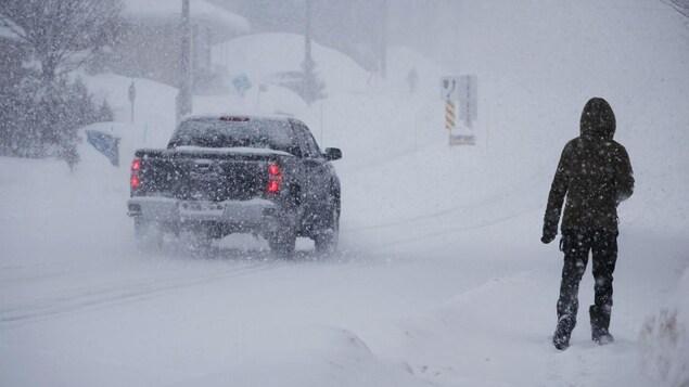 Une voiture et un piéton sur une route enneigée.