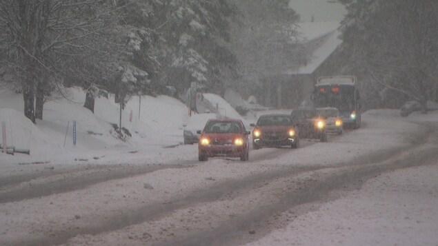 Des véhicules circulent sous la neige.