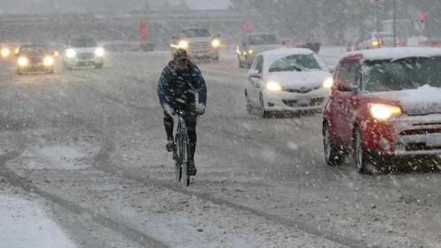 Un cycliste pédale sous la neige à Winnipeg.