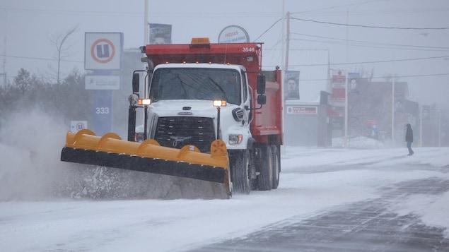 Un camion gratte la neige sur une rue de Rimouski.