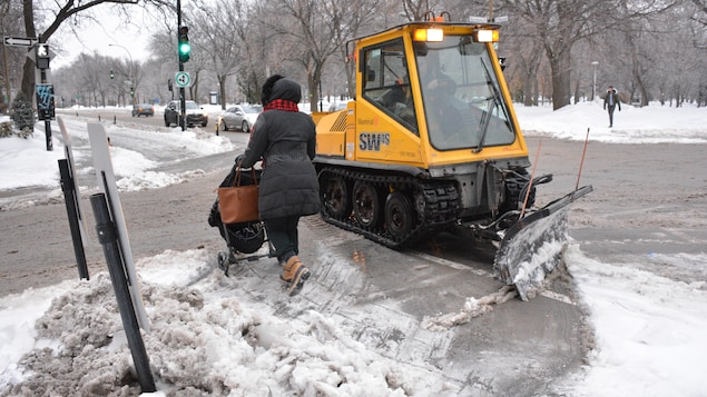 Une chenillette s'affaire à dégager les trottoirs de la Ville de Montréal.