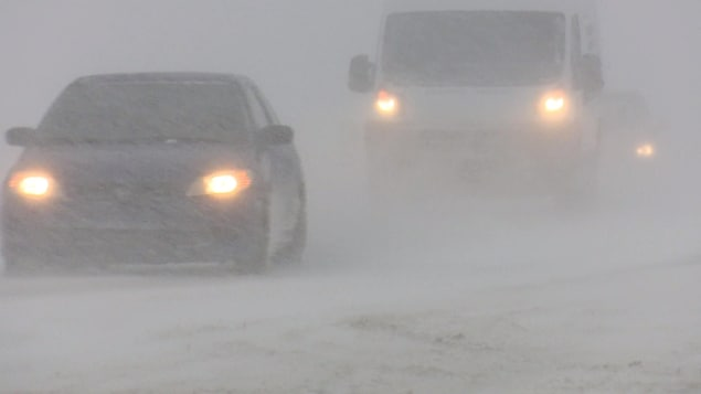 Deux voitures circulent durant la tempête.