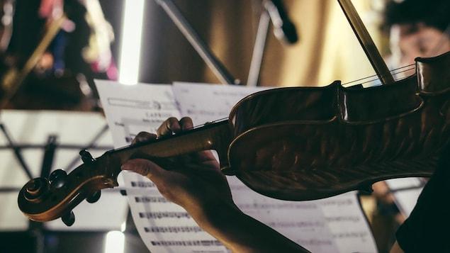 Une personne joue du violon au sein d'un orchestre.