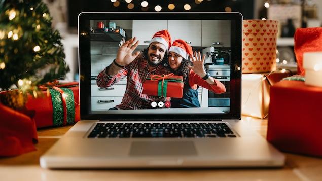 Un couple sur un écran d'ordinateur fête Noël par vidéoconférence avec un cadeau dans les mains.