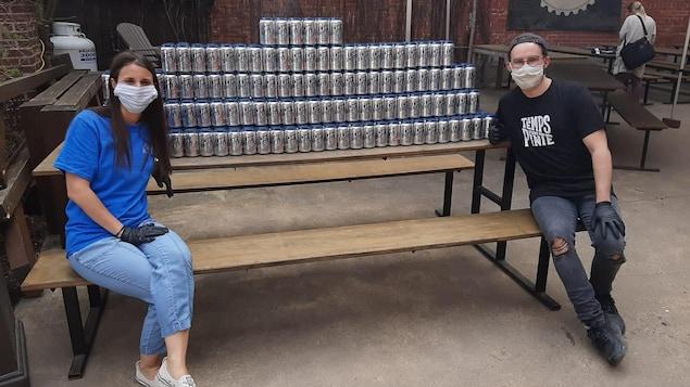 Deux employés sont assis sur une table à l'extérieur et présentent les bières à donner.
