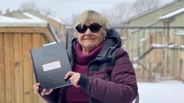 Une femme dehors, portant des lunettes de soleil et tenant dans ses mains un cahier noir.