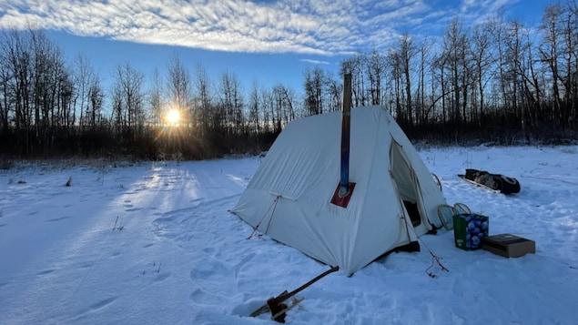Une tente installée sur de la neige au milieu de la nature.