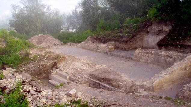 On voit une place rectangulaire excavée, entourée de murets de pierre, dans un site où la végétation est abondante.