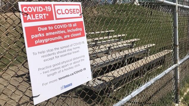 Un avis de fermeture des installations des parcs installé sur la clôture d'un terrain de baseball.