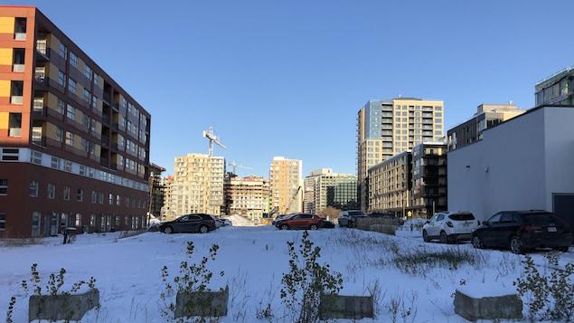 Un terrain vacant recouvert de neige, entre des immeubles.