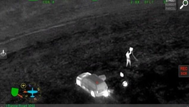 Image infrarouge où l'on aperçoit Terrance Morin dans un champ, près du véhicule qu'il a volé.