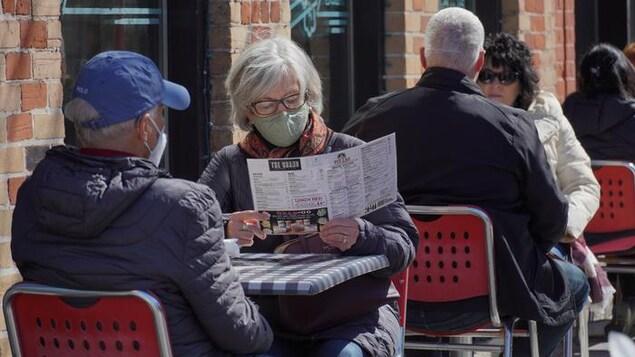 Un dame attablée sur une terrasse avec un homme consulte un menu. Tous deux portent le masque.