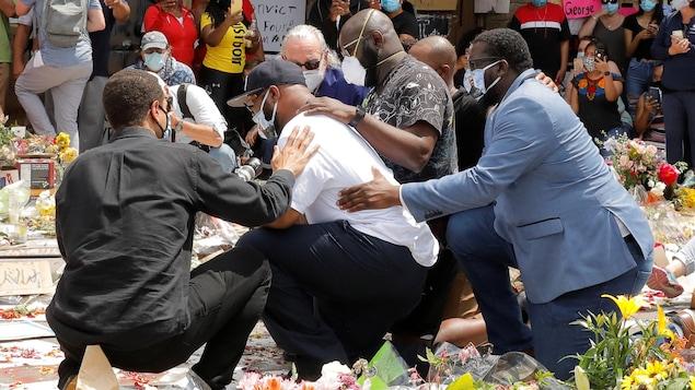 Terrence Floyd, portant un masque, est agenouillé en compagnie de proches. Il se recueille à l'endroit où son frère a été tué, où se trouvent plusieurs bouquets de fleurs.