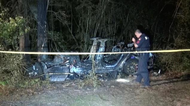 On voit la carcasse calcinée d'un véhicule qui a foncé dans un arbre. Un policier examine les restes de ce véhicule derrière un cordon de sécurité.