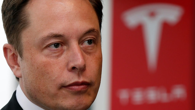 Elon Musk devant un logo de Tesla.