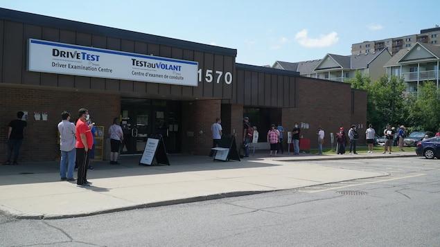 File de gens devant l'édifice où se trouve le centre.