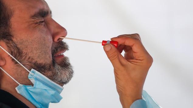 Un homme grimace lorsqu'on lui prélève de la narine un échantillon pour un test de dépistage de la COVID-19, le 22 septembre 2020 à Le Blanc-Mesnil, en France.
