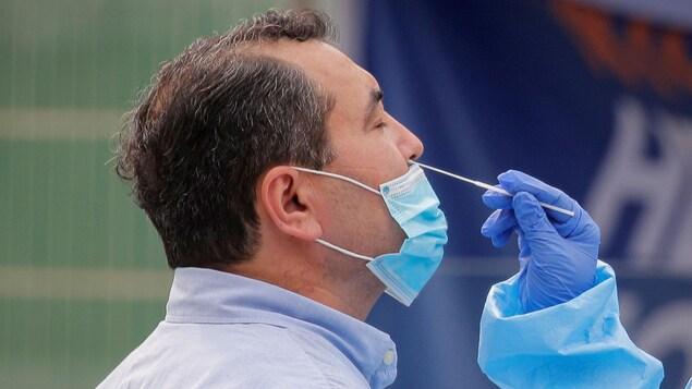 Une infirmière prélève un échantillon du nez d'un homme pour un test de dépistage de la COVID-19 dans un parc de Brooklyn le 25 septembre 2020.