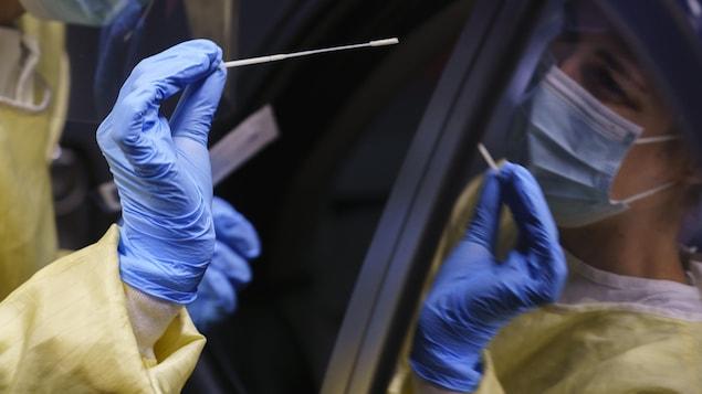 Une infirmière devant une voiture tient un instrument pour prélever un échantillon pour un test de dépistage. On voit son reflet dans la fenêtre fermée du véhicule.