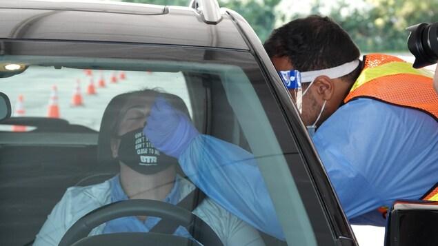 Un infirmier effectue un test sur une personne assise dans sa voiture.