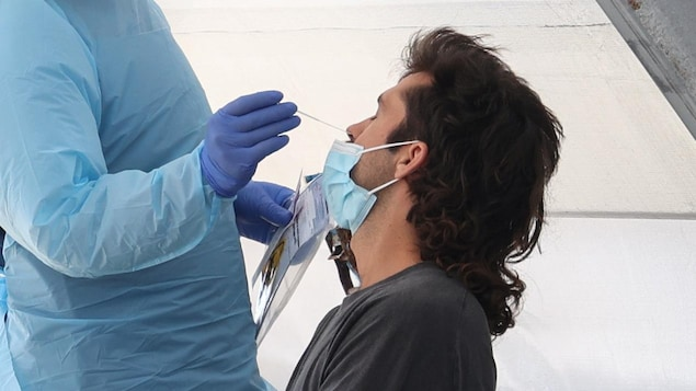 Un test de dépistage de COVID-19 est effectué auprès d'un homme arborant une coupe Longueuil.