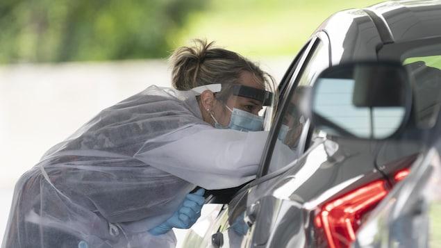 Une infirmière tend un écouvillon à l'intérieur d'une voiture.