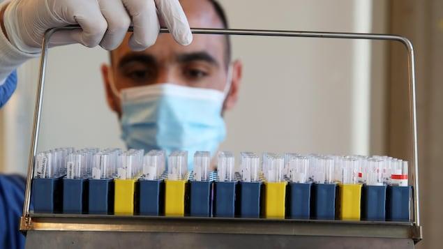 Un technicien de laboratoire tient un plateau rempli d'éprouvettes dans un hôpital de Liège, en Belgique, le 3 novembre 2020.