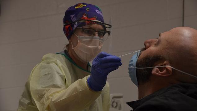 Une infirmière fait un prélèvement dans la cavité nasale d'un patient.