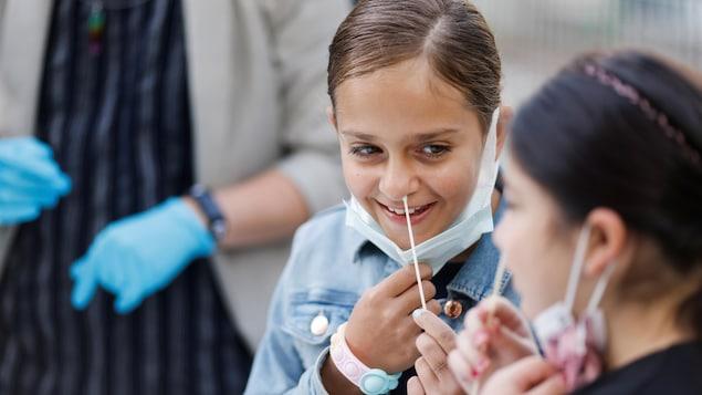 Une enfant souriante insère une tige dans sa narine gauche.