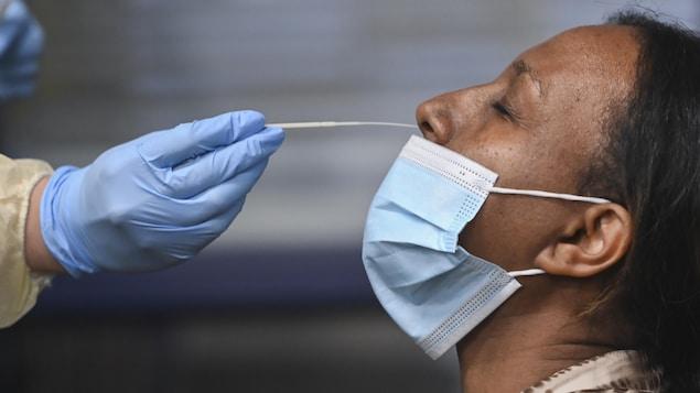 Une travailleuse de la santé insère un coton-tige dans le nez d'une patiente pour le prélèvement d'un échantillon pour un test de dépistage.