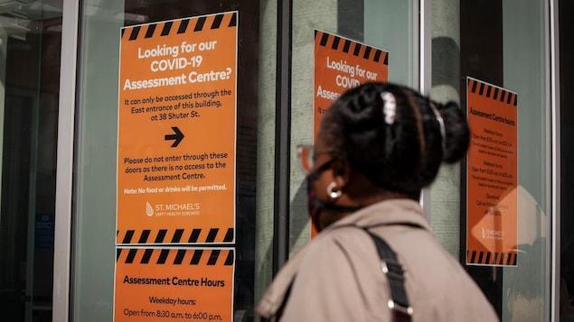 Une femme devant une affiche expliquant le protocole de diagnostic.