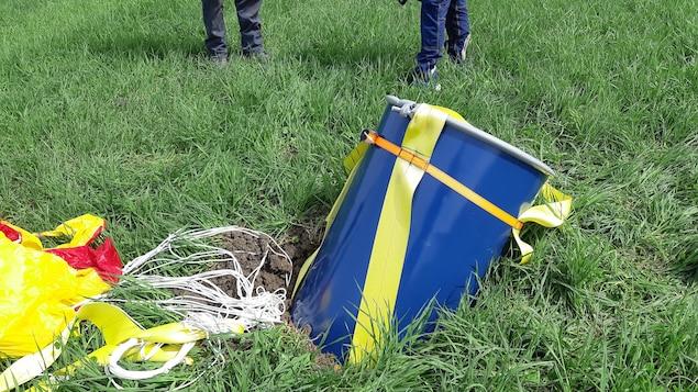 Un baril bleu attaché à un parachute jaune et rouge écrasé dans un champ.