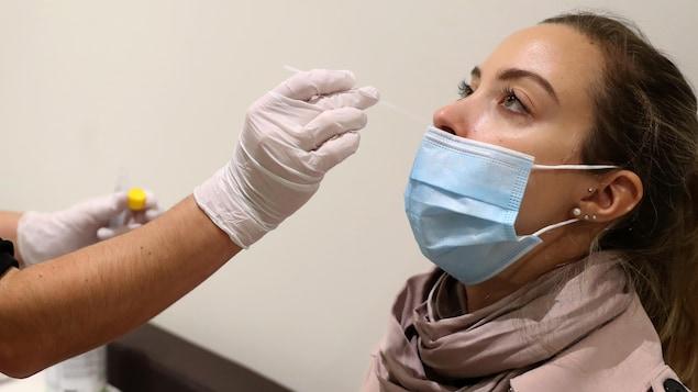 Une infirmière prélève un échantillon de la narine d'une patiente pour un test de dépistage de la COVID-19 le 19 octobre 2020, à Zurich, en Suisse.