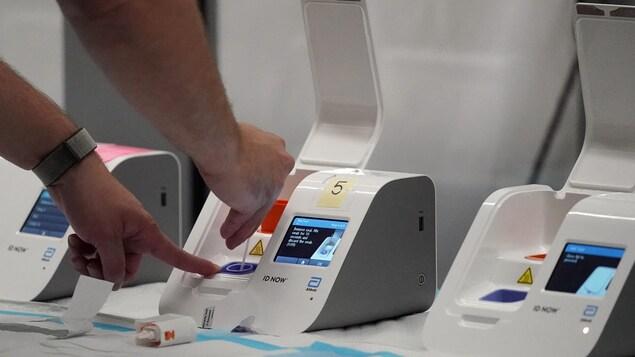 Un travailleur de la santé utilise un petit appareil pour faire le test.