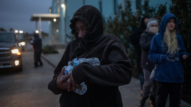 Une femme transporte des bouteilles d'eau qu'elle a reçues d'un refuge.