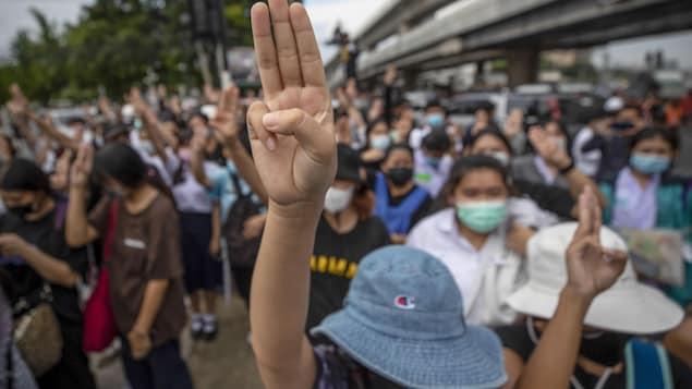 Une manifestante fait le salut à trois doigts au milieu d'une foule.