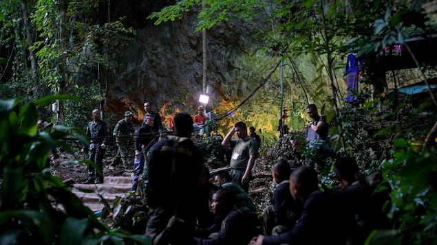 Des hommes se tiennent dans une forêt.